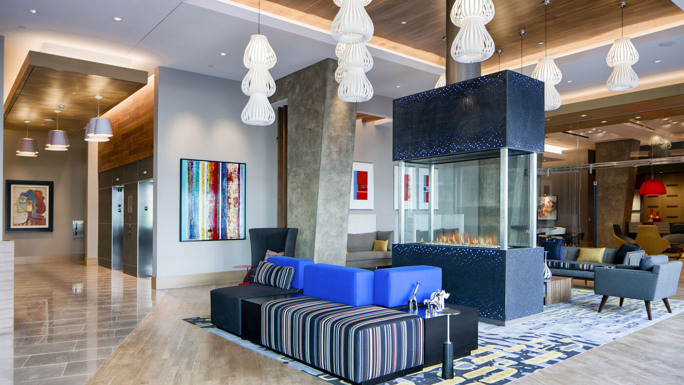 Inviting lobby with open seating, large-screen TVs, and a glass fireplace centerpiece.