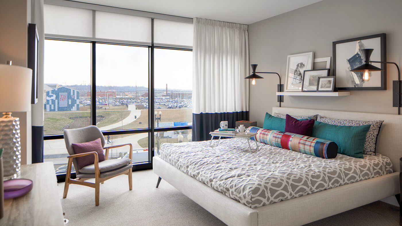 Light filled bedrooms with floor-to-ceiling glass windows offering gorgeous waterfront views